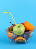 Glass bowl with fruit for diet on blue background — Stock Photo