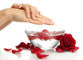 Woman hands with glass bowl of water with petals, isolated on white — Стоковое фото