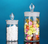Capsules and pills in receptacles on blue background — Stock Photo