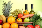 Composition with vegetables and fruits in wicker basket on green background — Stock Photo