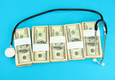 Healthcare cost concept: stethoscope and dollars on blue background — Stock Photo