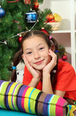 Little girl dreaming near christmas tree — Stock Photo