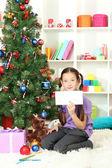 Little girl writing letter to Santa near christmas tree — Стоковое фото