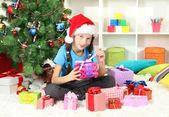 Little girl holding gift box near christmas tree — Стоковое фото