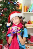 Little girl with pink scarf and cup of hot drink sitting near christmas tree — Photo