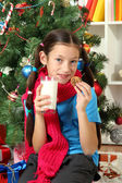 Little girl with pink scarf and glass of milk sitting near christmas tree — Stok fotoğraf
