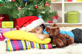 Little girl sleeping near christmas tree — 图库照片