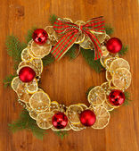 Christmas wreath of dried lemons with fir tree and balls, on wooden background — Foto de Stock