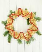 De kroon van kerstmis van gedroogde citroenen met fir tree, op witte houten achtergrond — Stockfoto