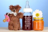 Baby bottle with fresh juice, puree and teddy bear on blue background — Stock Photo
