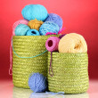 Colorful yarn for knitting in green basket on red background — Stock Photo