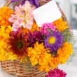 Beautiful bouquet of bright flowers in basket with paper note on white table on window background — Stock Photo