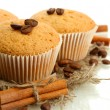Tasty muffin cakes on burlap, spices and coffee seeds, isolated on white - Photo