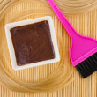 Hair dye in bowl and brush for hair coloring on beige bamboo mat, close-up — Stock Photo