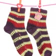 Pair of knit striped socks hanging on a rope isolated on white - Foto Stock
