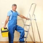 Handyman in house near the wall — Stock Photo #16326229