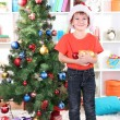 Little boy in Santa hat decorates Christmas tree in room - Stock Photo