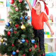 Little boy in Santa hat decorates Christmas tree in room — Stock Photo #16326507