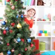 Little boy in Santa hat peeks out from behind Christmas tree - Foto Stock