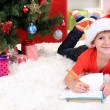Little boy in Santa hat writes letter to Santa Claus - Foto de Stock  