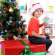 Little boy with big gift and clock in anticipation of New Year - Foto Stock