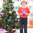 Little boy in Santa hat stands near Christmas tree with gift in his hands - Stock Photo