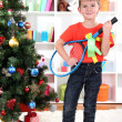 Little boy stands near Christmas tree with badminton rackets - Zdjęcie stockowe