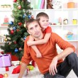 Father and son near Christmas tree - Foto Stock