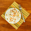 Risotto on color plate on wooden background — Stock Photo #16326565