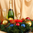 Beautiful Christmas wreath in composition with champagne on gold fabric background - Stock fotografie