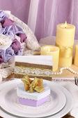 Mesa de casamento fabuloso servir na cor púrpura e ouro sobre fundo de tecido branco e roxo — Fotografia Stock