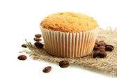 Tasty muffin cake on burlap and coffee seeds, isolated on white — Stock Photo