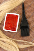 Hair dye in bowl and brush for hair coloring on brown bamboo mat, close-up — Stock Photo
