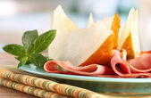 Parma ham and melon, on wooden table — Stock Photo