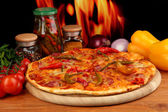 Tasty pepperoni pizza with vegetables on wooden board on flame background — Stock Photo