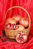 Ripe pomegranates on basket on red cloth background — Stock Photo