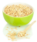 Green bowl full of oat flakes with wooden spoon isolated on white — Stock Photo