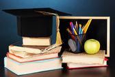 Libros y magister tapa contra junta escolar sobre tabla de madera sobre fondo azul — Foto de Stock