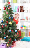 Little boy in Santa hat peeks out from behind Christmas tree — Stockfoto