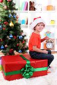 Mały chłopiec z wielkim darem i zegar w oczekiwaniu na nowy rok — Zdjęcie stockowe