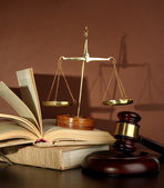 Golden scales of justice, gavel and books on brown background — Foto Stock