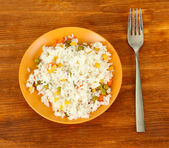 Risotto on color plate on wooden background — Stock Photo