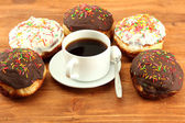 Tasty donuts on color plate on wooden background — Stock Photo