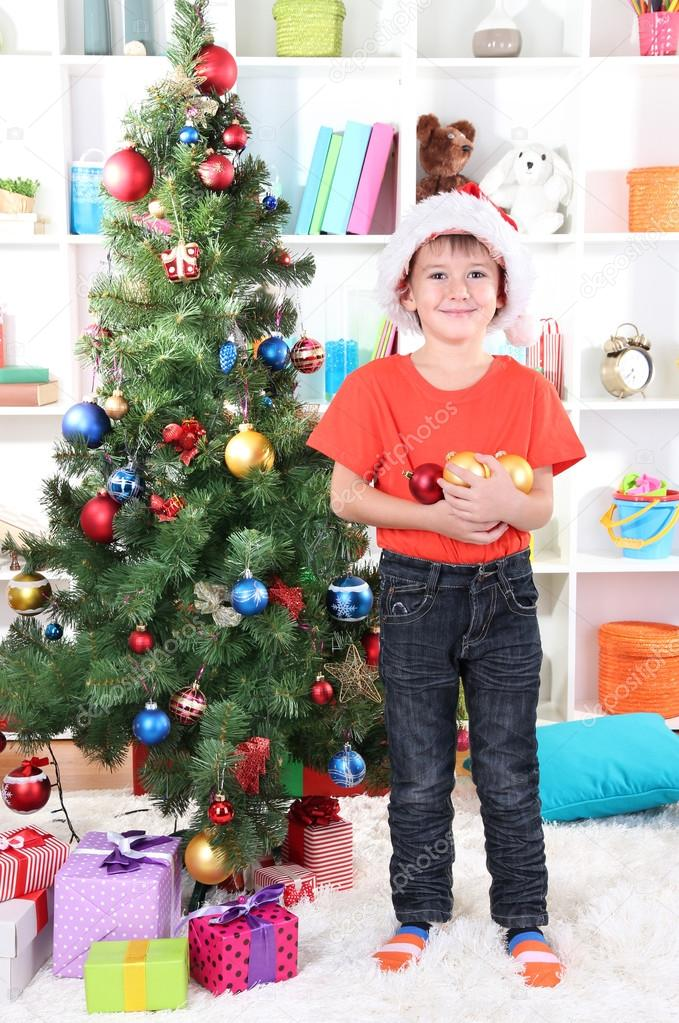 Little boy in Santa hat decorates Christmas tree in room — Stock Photo #16326503