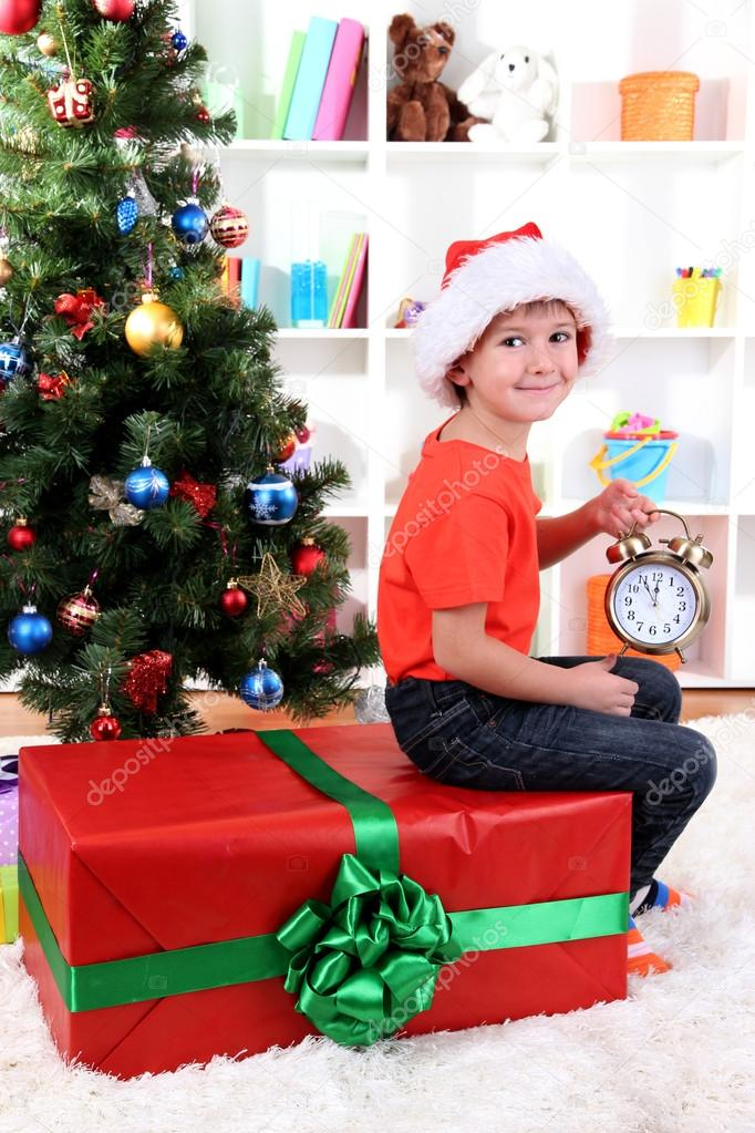 Little boy with big gift and clock in anticipation of New Year  Stock Photo #16326523