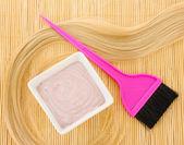 Tinte de pelo en el tazón y cepillo para colorante de pelo en la estera de bambú beige, close-up — Foto de Stock