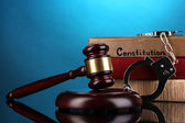 Gavel, handcuffs and books on law on blue background — Stock Photo