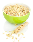 Green bowl full of oat flakes with wooden scoop isolated on white — Stock Photo