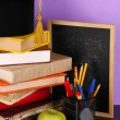 Books and magister cap against school board on wooden table on purple background — Stock Photo #16601161