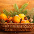 Christmas composition in basket with oranges and fir tree, on wooden background - Stock fotografie
